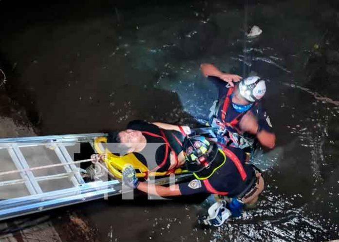 Momento cuando el joven estaba siendo rescatado del cauce en Managua