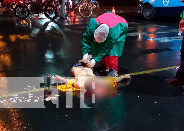 La forense revisando el cuerpo del fallecido en la entrada a Chinandega