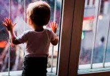 Menor de edad frente a una ventana