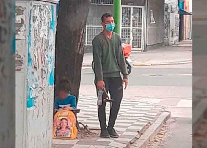 Viral: Niña hace su tarea en la calle, mientras su papá limpia carros