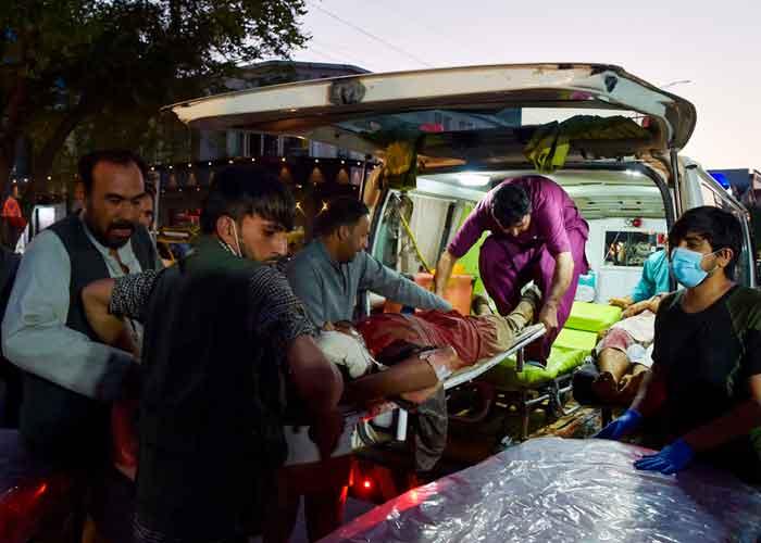 Voluntarios y personal médico trasladan a un herido para que reciba tratamiento tras dos potentes explosiones