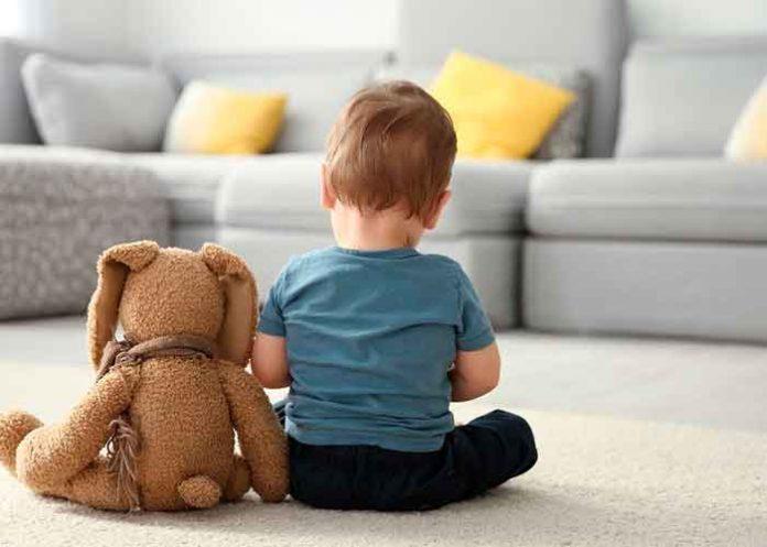 Niño que sufre autismo junto a un peluche