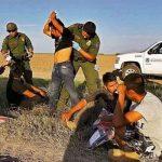 Agente policial de la frontera revisando a un grupo de migrantes