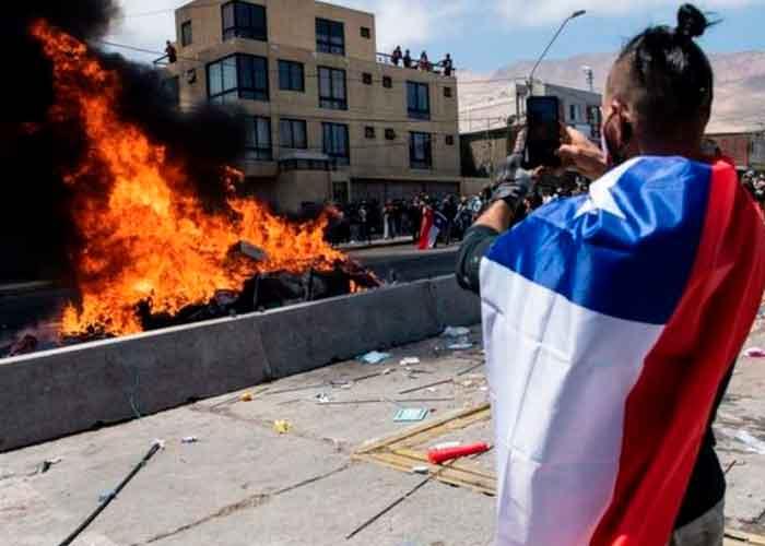 Foto: Un ciudadano toma una imagen de la quema de ropa y pertenencias de los extranjeros que han llegado a Iquique en los últimos meses.