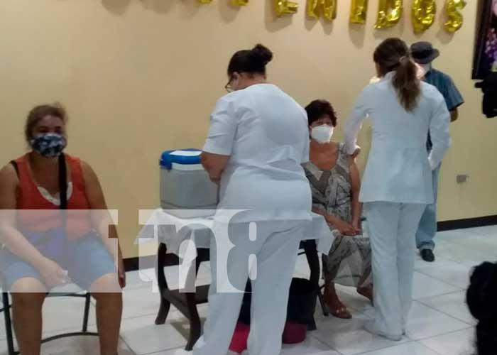 Personas mayores de 30 años de edad se llegan a vacunar para evitar el COVID-19
