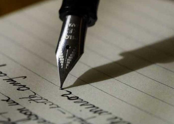 Pluma escribiendo sobre una hoja de papel